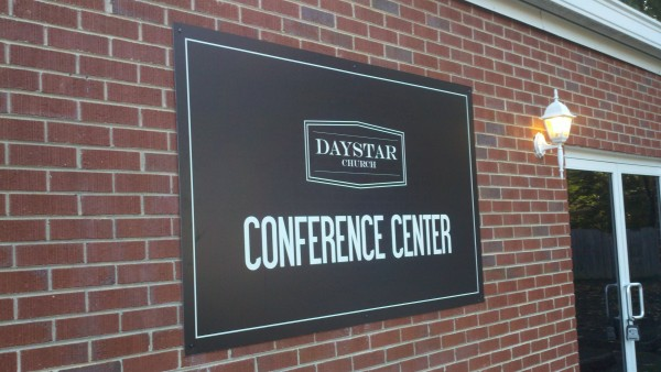 Black Aluminum Sign Mounted on Brick Wall